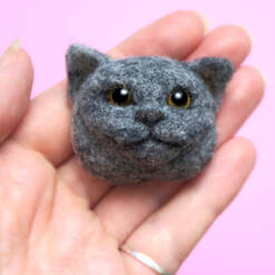 A needle felted British Blue Shorthair face brooch by Little Grassbird resting on a hand against a pink background