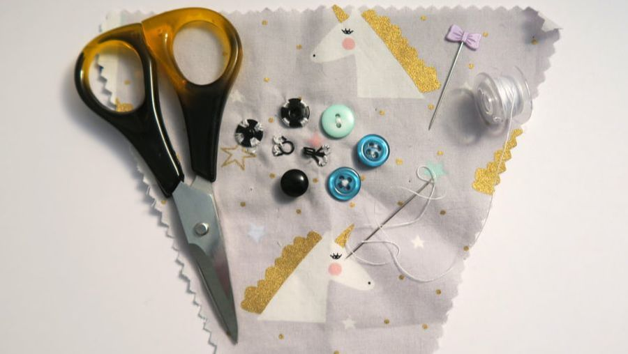 Scissors, press studs, buttons, hook and eye, pin, needle, thread, and bobbin on unicorn fabric